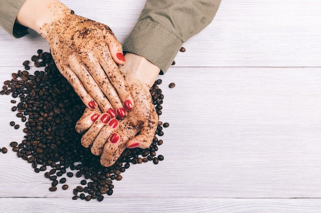 Close-up of a woman applying coffee scrub to her hands