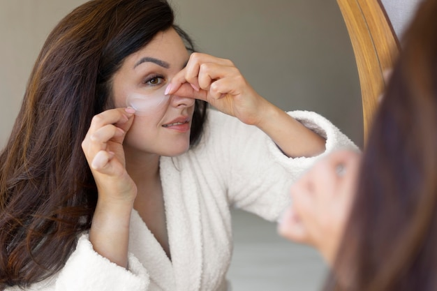 Close up woman applying eye patch