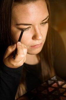 Close-up of a woman applying eye shadow