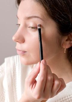 Close-up woman applying eyeshadow
