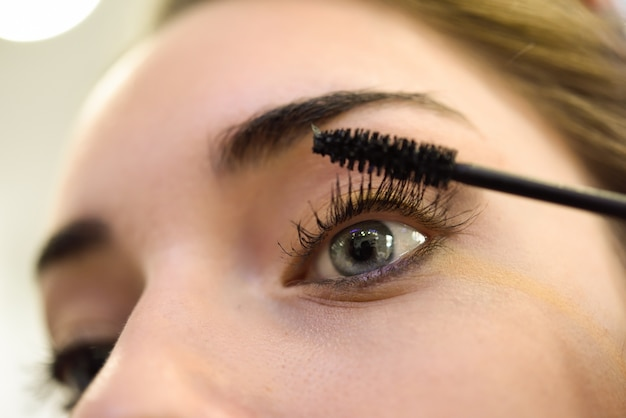 Close-up of woman applying mascara to her lashes