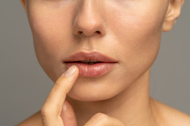 Close up of woman applying moisturizing nourishing balm to her lips with her finger