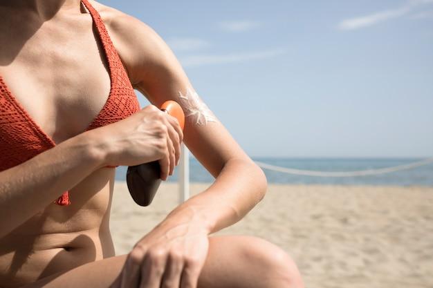 Крупным планом женщина, применяя солнцезащитный крем на теле