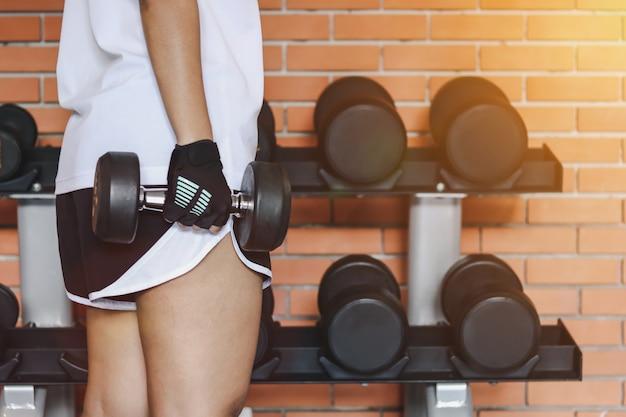 Крупным планом женщина поднимает гантели в фитнес-зале с гантелями на стойке