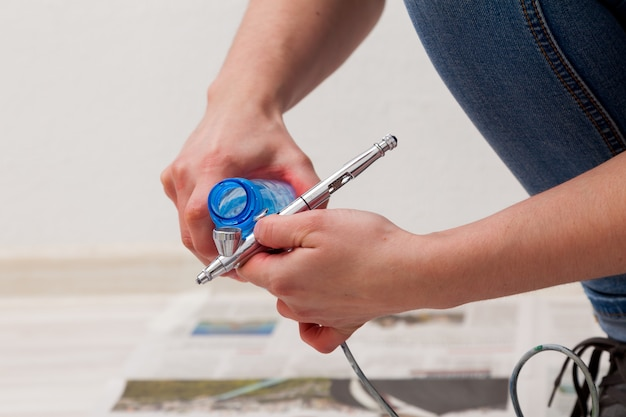 Close-up of a woman artist in jeans cleans and prepares the airbrush for the work of painting the walls.