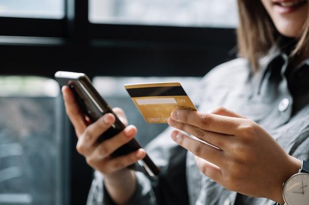Крупным планом женщина дома, делая покупки в интернете с помощью кредитной карты и смартфона