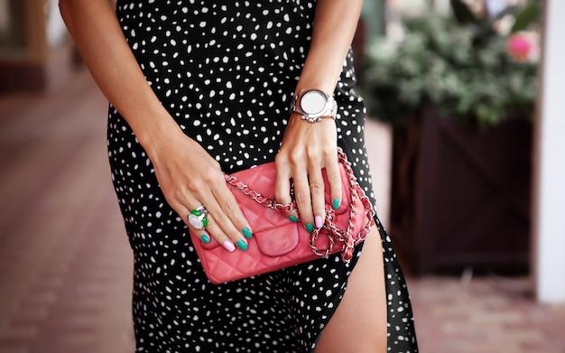 손 모델에 여자 가방을 닫습니다 세련된 소녀는 시계 반지 녹색과 분홍색 매니큐어를 가지고 있습니다