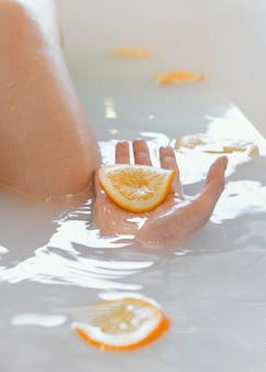 Close up woman bathing with orange slices in water