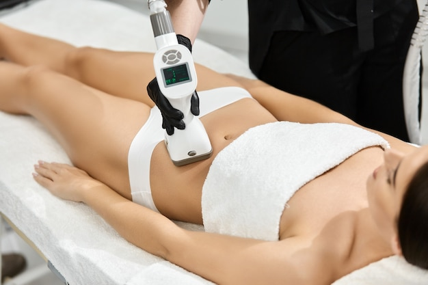 Close-up of woman belly with professional massager