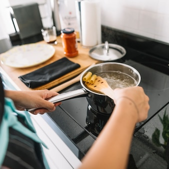 Close-up of woman boiling rigatoni pasta on electric stove