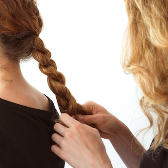 Close-up of woman braiding sister's hair against white background