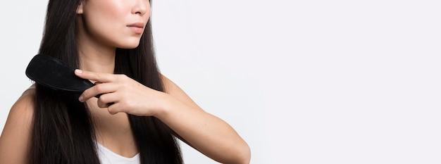 Close-up woman brushing hair