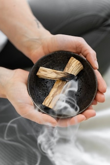 Close-up of woman burning sage at home for relaxation
