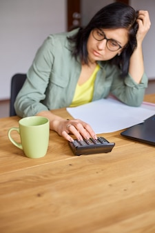 Close up of woman calculates expenses on calculator at wooden table