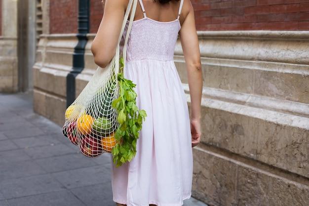 야채와 함께 가방을 들고 여자를 닫습니다