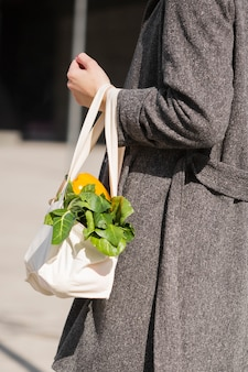 Close-up woman carrying ecological bag with vegetables