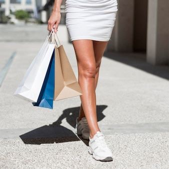 Close-up woman carrying shopping bags