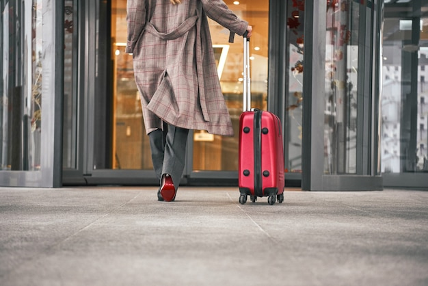 Close up of woman carrying suitcase at the airport terminal and hurrying up for check in on holiday or business trip.