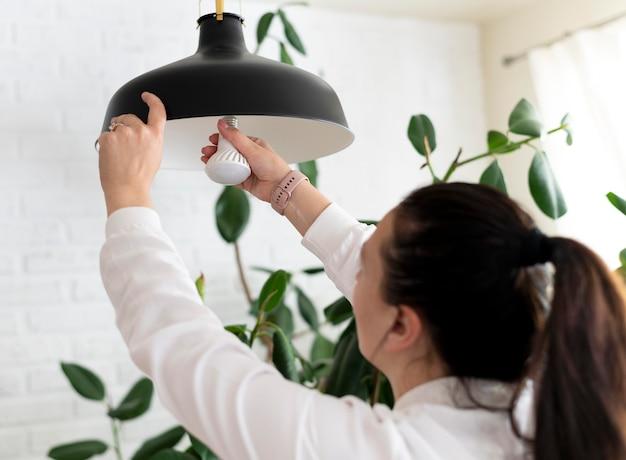 電球を変更する女性をクローズアップ