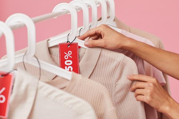 Close-up of woman choosing clothes on the rack and buying them on sale