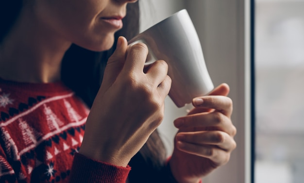 Close up of a woman in a christmas sweater holding a mug by the window