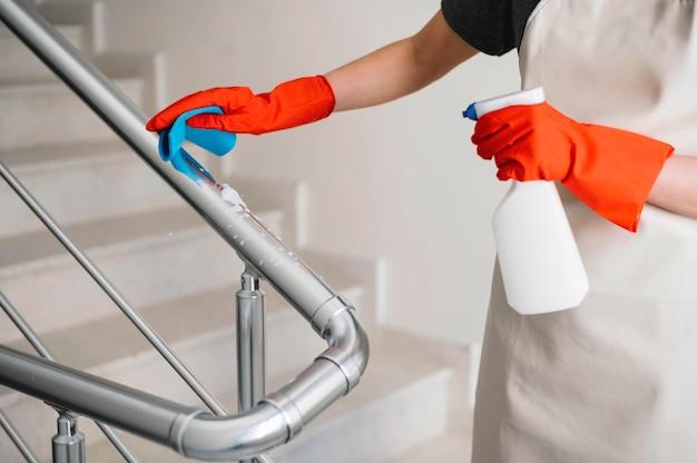 手すりを掃除するクローズアップの女性