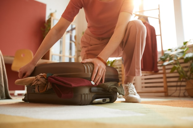 Close-up of woman closing her suitcase with clothes preparing for journey