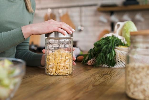 Close-up woman closing jar with organic pasta