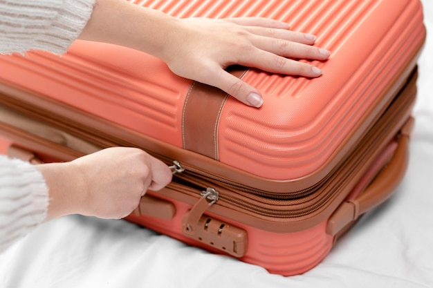 Close up woman closing luggage
