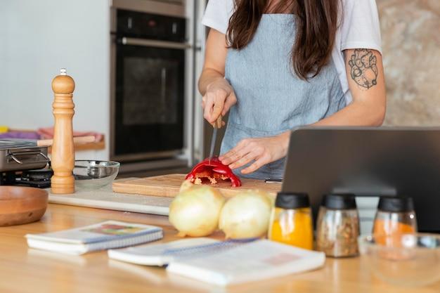 Chiuda sulla donna che cucina nella cucina