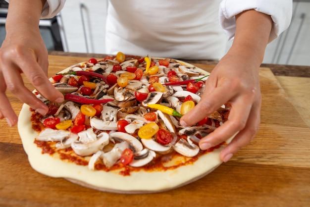 여자 요리 피자를 닫습니다