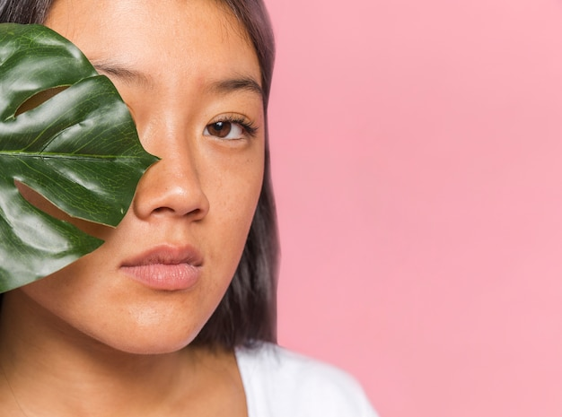 Close-up woman covering her eye with monstera leaf