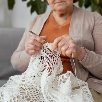 소파에 crocheting 여자를 닫습니다