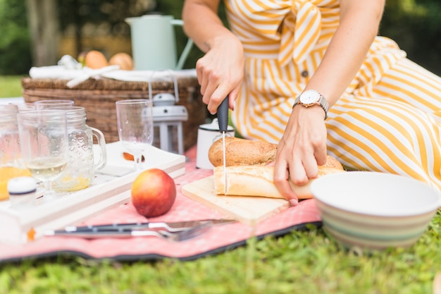 Close-up of woman cutting bread with knife on picnic