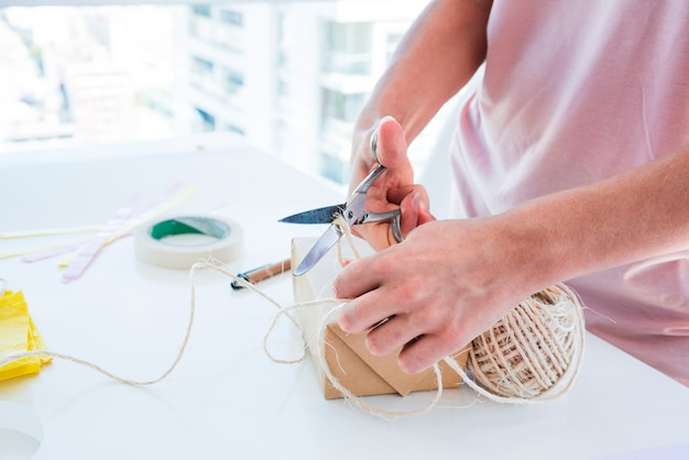 Close-up of a woman cutting the thread from spool with scissor on white table