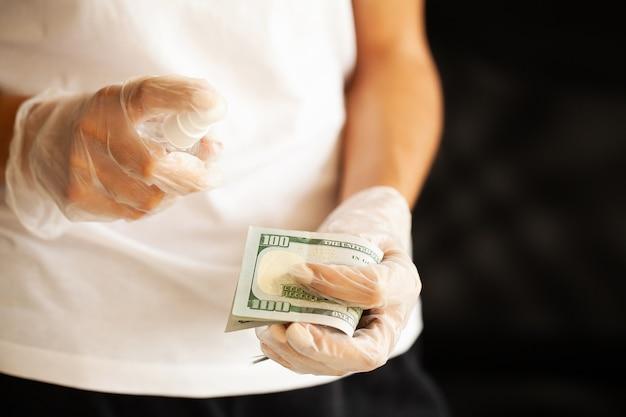 クローズアップの女性は消毒剤でお金を消毒します。