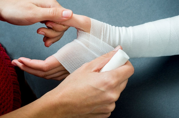 Close-up of woman doctor bandaging a hand