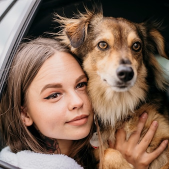 Close up woman and dog looking through car window