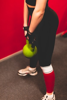 Close-up of a woman doing exercise with kettlebell