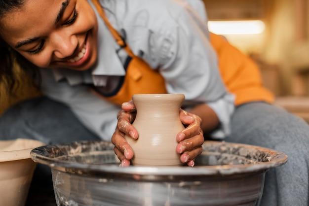 Chiuda sulla donna che fa ceramiche