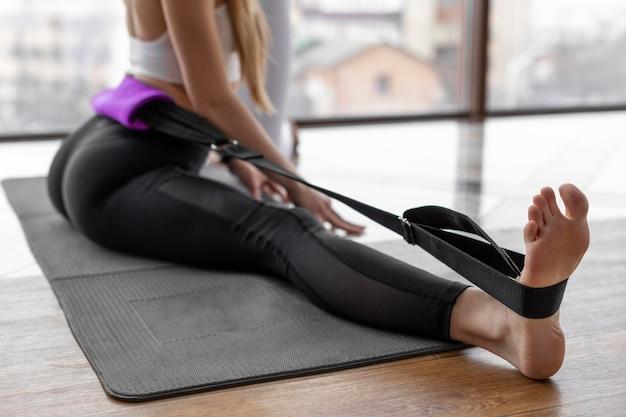 Chiuda sulla donna che fa yoga sulla stuoia