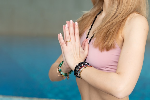 Close up of woman doing yoga poses, hands gesture near swimming pool