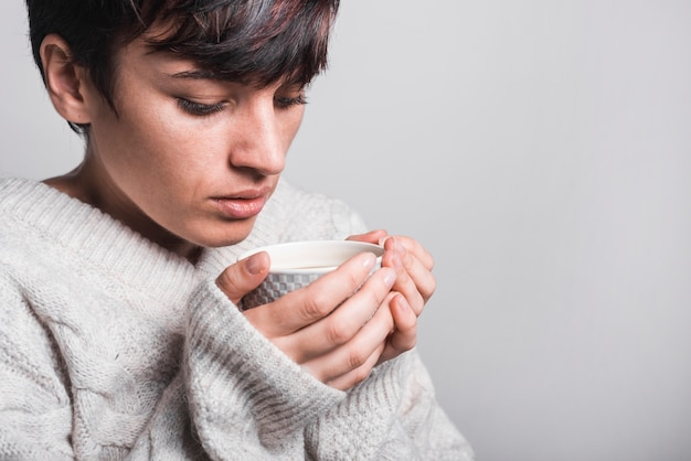 Close-up of woman drinking coffee against gray background