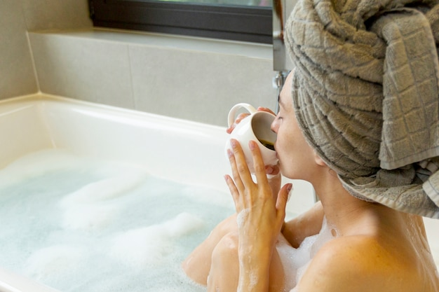 Close-up woman drinking coffee in the bathtub