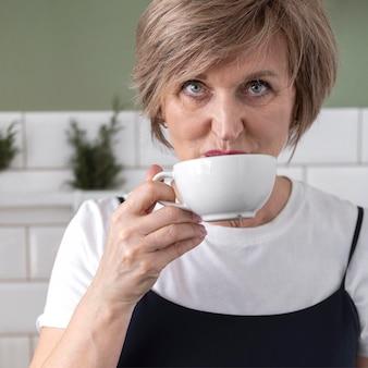 Chiuda sulla donna che beve dalla tazza