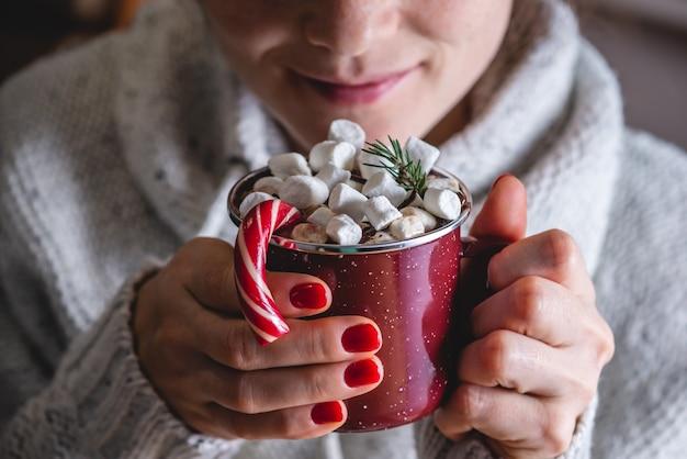 마쉬 멜 로우와 핫 초콜릿을 마시는 여자를 닫습니다
