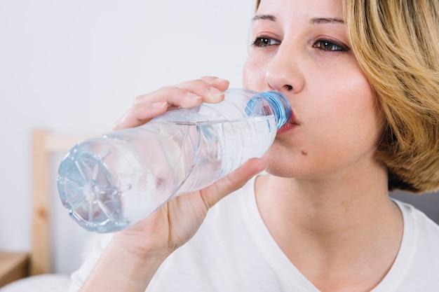 Acqua potabile della donna del primo piano dalla bottiglia
