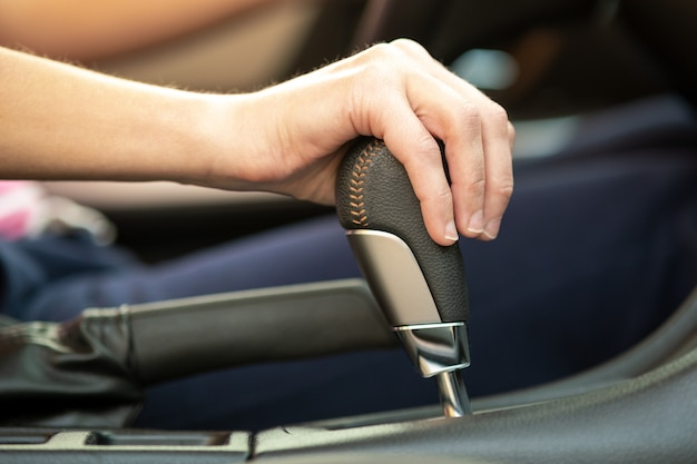 Close up of woman driver holding her hand on automatic gear shift stick driving as car