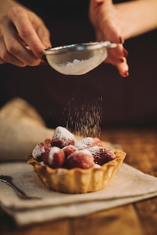 Close-up of woman dusting the sugar powder on strawberry tart