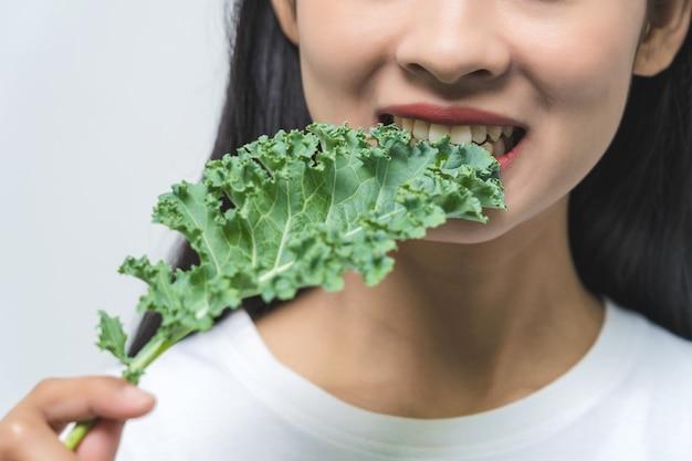 クローズアップ女性はケールの葉を食べる、スタジオで菜食主義者。